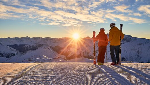 Skiers enjoy after a exciting skiing day the sunset in the ski area of Ischgl