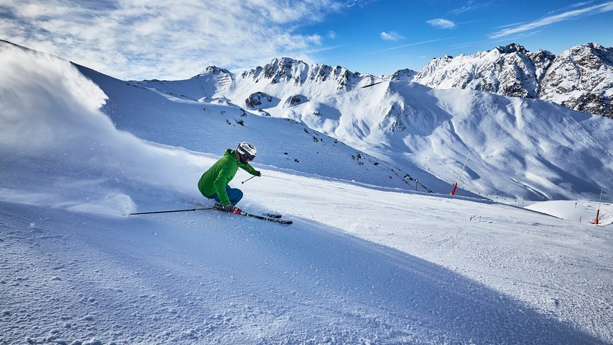 Skier drives down a slope of the ski area of Ischgl