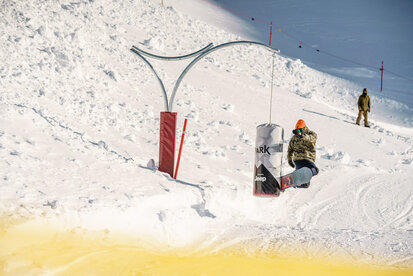 Snowboarder have fun by making jumps in Parkarea in Ischgl