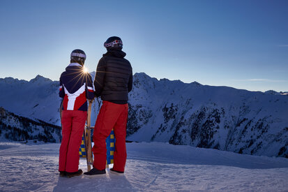 Couple enjoys together the sunset and stunning mountain panorama of Ischgl before tobogganing