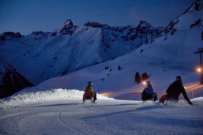 Holidaymakers have fun at the night-time toboggan run in Ischgl