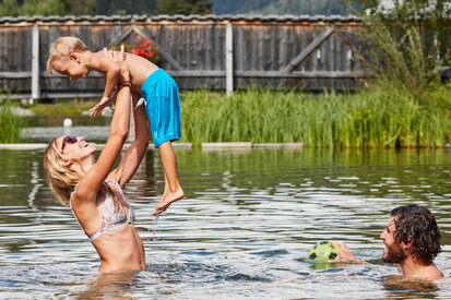 Families enjoy playing in the water in the lake of See